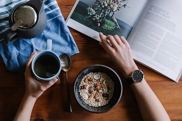 Listující žena v knize, aby našla motivaci na zdravou stravu, konkrétně na snídani