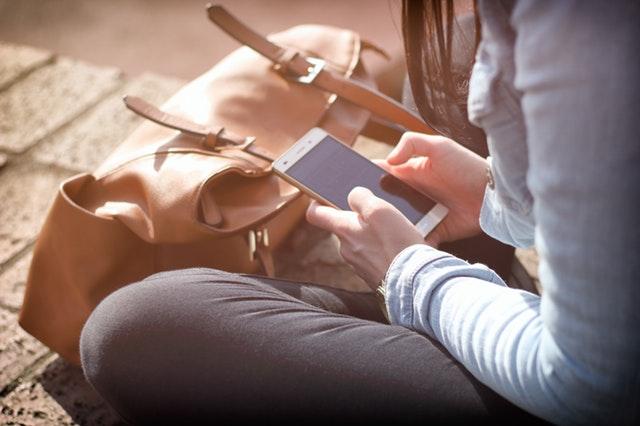 Dívka sedící na zemi, držící telefon v ruce